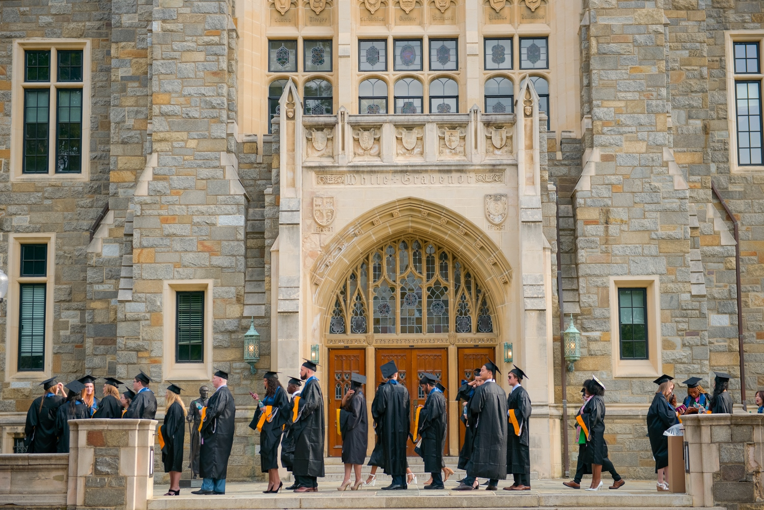 graduate students in commencement regalia line up in front of carved stone doorway at White-Gravenor Hall